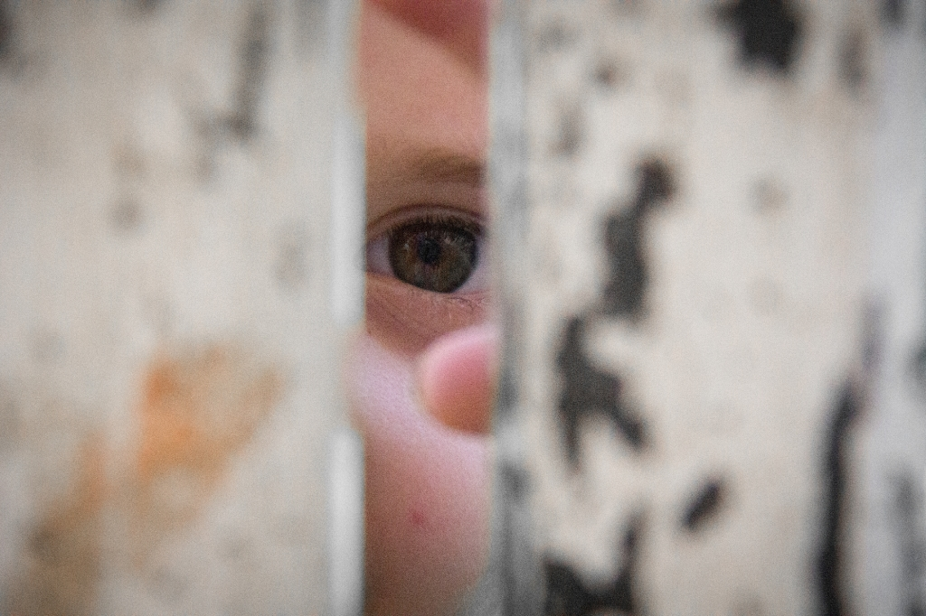 """5/52-The challenge was lots of negative space. I have some great shots from previous weeks that do this well but this week was tricky. I was shooting at an event where there were so many people that shooting negative space was """"almost impossible"""". Love this picture of my three year old playing peekaboo through the metal poles!"""